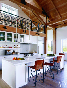The kitchen of a Martha's Vineyard residence designed by Ariel Ashe and Reinaldo Leandro features a Sub-Zero refrigerator, a Wolf range, and Dornbracht sink fittings; the minimalist pendant lights are by Davide Groppi, the Bernard-Albin Gras sconces are by Design Within Reach, and the barstools are by Garza Marfa.