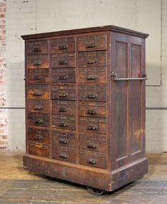 Rolling distressed apothecary wood storage cabinet, vintage Industrial with brass hardware. Lower six drawers are double drawers. Cabinet is on four cast iron wheels, two are swivel. Overall dimensions measure 40 x 25 x 53 Vintage Industrial Furniture, Rustic Furniture, Antique Furniture, Modern Furniture, Luxury Furniture, Office Furniture, Outdoor Furniture, Industrial Dining, Victorian Furniture