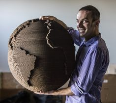 Dan Shapiro founded Glowforge, which makes 3-D laser printers for designers. He's holding a recycled cardboard lamp made with the printer. (Steve Ringman/The Seattle Times)