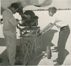 Amelia Earhart observing a mechanic :: Amelia Earhart Papers (George Palmer Putnam Collection)