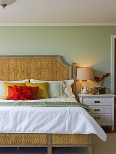In this sage green bedroom, a tan wicker bed and headboard is topped with green and white bedding, decorated with a slew of pillows that include red and gold pillows, and positioned next to a wood side table on which has a clear table lamp and sea shells. Tropical Bedrooms, Coastal Bedrooms, Beach Bedrooms, Master Bedrooms, Modern Paint Colors, Bedroom Paint Colors, Wall Colors, Paint Colours, Beach Bedroom Decor