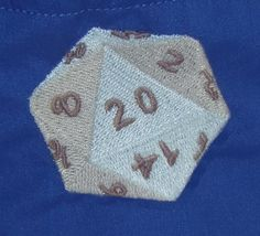 """This pouch has a machine embroidered blue/gray D20 on it. The outer fabric is blue with a blue & white lining fabric. This pouch is 6 1/2"""" high, 4"""" round. It will stand open on the game table. It has a white shoe lace drawstring on 2 sides. Embroidery pattern is from Urban Threads."""