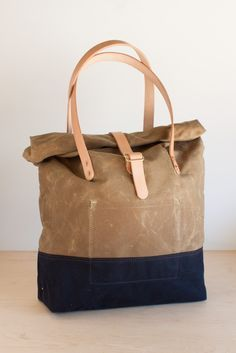 Made from waxed cotton canvas and Hermann Oak natural veg-tan leather. Two interior pockets, double bottom layer, hand-hammered copper rivets and all raw fabric edges bound with twill tape. Leather st