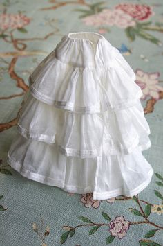 Underwear... On a background of organdy to support the fullness, the petticoat deploys its three cotton voile flounces, each bordered with two rows of silk ribbon.