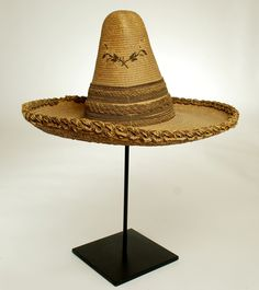 Fancy Mexican Sombrero | Fancy Mexican Sombrero - #6692 Extremely fine and rare late 19th century hand caned Mexican sombrero with fiber cord and braided rope meticulously wrapped in metallic thread. Northern Mexico, possibly California - circa 1890. Displayed on a high quality custom made stand.  Dimensions: overall height on stand is 23 inches. Sombrero measures 17.5 inches diameter.  Condition: loose brim threads.