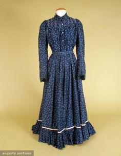 BLUE KITE PRINTED WRAPPER, LATE 19th C Woman's gown of soft cotton, medium blue printed with diamonds and squiggly lines, trimmed with white cotton woven tape and embroidery, high fold down collar, tucks at shoulders, releasing into bodice fullness, tucks overstitched at front closure to below waist with buttoned under bodice, long sleeves slightly gathered at top, front tie belt attached at back with tabs suggesting bustle, deep flounced hem, trained skirt