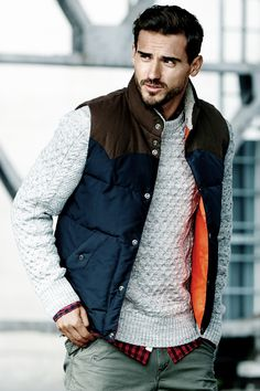 A true style icon, the puffer vest is a versatile & fashionable addition to your transitional wardrobe. Dark blue padded vest with stand-up collar and gray cable-knit sweater.│ H&M Men.