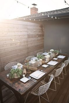 vintage metal chairs, rustic table, & flowers on terrace. Really like the wood they used on the back wall/fence