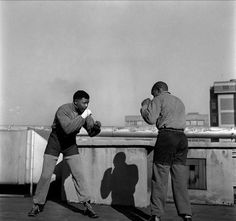 """""""Young Nelson Mandela boxing on a roof top in Johannesburg during a break from the Treason Trial in Photo by Bob Gosani, Treason Trial: End of Round One, 1957"""