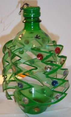 Take a large or small green pop bottle with lid. Draw zigzag verticle lines up the bottle every inch.X-mas soda bottle wind spinner. Zigzag cuts, pain on edges and lid.Garden Wind Spinners and Whirligigs – Make Some For Spring!Green spinner - looks Pop Bottle Crafts, Plastic Bottle Crafts, Recycle Plastic Bottles, Plastic Craft, Recycled Bottles, Recycled Crafts, Crafts To Make, Crafts For Kids, Diy Crafts