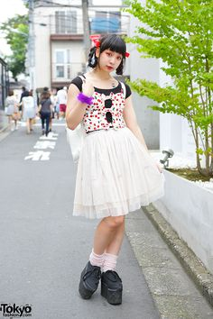 """"""" 17-year-old Pani on the street in Harajuku with a double braids hairstyle, cherry print corset top, a Swimmer tulle skirt, and Spinns platform sneakers. """""""