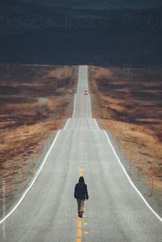 Woman walking away on an empty desolate road to Cape North, Norway. by Luca Pierro for Stocksy United