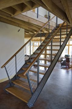 Cool banister - industrial stairs with stainless cable railing. handrail to match wood stair tread.