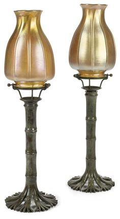 A pair of Tiffany Studios Favrile glass and patinated bronze Bamboo candlesticks  1899-1918  green brown patina, shades inscribed L.C.T., bases impressed TIFFANY STUDIOS NEW YORK 1205