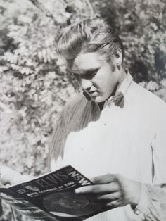 Elvis with natural hair, reading about himself.