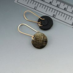 A lightweight, modern earring in etched polymer clay in a lilypad shape on elongated french earwires. The faux metal surface has gold and black tones. The back is matte black polymer. The earwires are handmade of 20 gauge 14K gold filled wire. The disc is 3/4 inch across and the earrings hang a total of 2 inches from the top of the earwire.