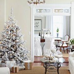 Play up a minimal living room for the holidays with brown, gold, and silver accents. A frosted Christmas tree displays oversize silver and gold ornaments; white and brown wrapped packages are placed neatly beneath the tree. A glass-top coffee table holds tall apothecary jars filled with white candies and Christmas cookies.