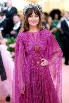 "Dakota Johnson on the 2019 Met Gala Celebration red carpet. On May the 2019 Met Gala occurred and the theme for this year's event was ""Camp: Notes on Fashion"" which challenged celebrities to deliver over-the-top outfits. Dakota Johnson, Don Johnson, Melanie Griffith, Maroon Dress, Pink Dress, Christian Dior, Saint Laurent, Camping Style, Chris Martin"