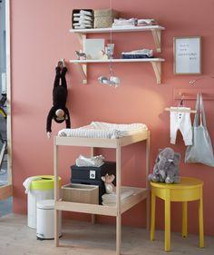 Nahaufnahme eines Wickelbereichs mit Windeln, Babykleidung und SNIGLAR Wickeltisch in Buche/Weiß