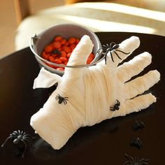 From the Grave-fill a white disposable glove with cotton balls, pushing them into the fingers.  Once the glove is full and sturdy, fold up the end of the glove and tape to secure.  Wrap 2 in wide gauze (you'll need approx 5 yards) around the fingers, hand, and wrist until completely covered, securing the end with a knot.  Use an extra cottong ball to apply brown chalk to the hand to give it an aged look.  Add creepy, crawly plastic bugs for a fresh from the ground look.