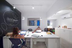 agência de pesquisa em casa de vila reformada, com iluminação em trilhos, piso de cimento queimado, parede com tinta lousa