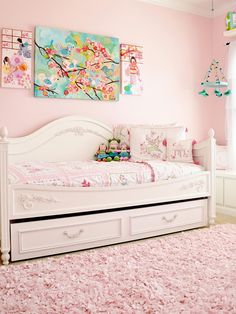 A daybed with trundle is a smart option for a small space girl's room since it takes up less room, but also provides an extra bed for sleepovers. A trio of artwork above the bed adds a punch of color to the light pink room. Girls Daybed Room, Pink Bedroom For Girls, Pink Bedrooms, Little Girl Rooms, Daybed Comforter Sets, Daybed Sets, Daybed Covers, Upholstered Daybed, Light Pink Rooms