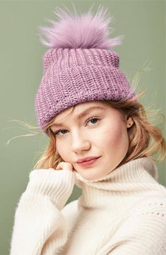 A soft faux fur pom tops off a chunky knit beanie that can be cuffed for extra ear coverage.