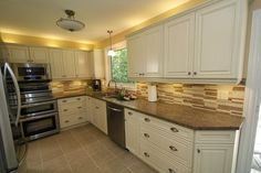 Cream kitchen cabinets with stainless steel appliances. Design by ...