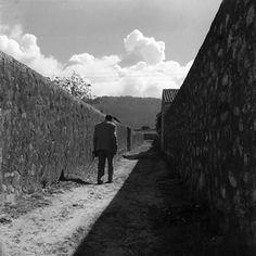 """Fernando Lemos """"António Pedro"""", 1949 Fotografia sobre Papel Agfa  «António Pedro da Costa, encenador e estudioso de teatro, quando soube que Fernando Lemos partiria sem volta para o Brasil, saiu caminhando em linha recta pelas azinhagas da cidade. Vou chorar no moinho, foi o que disse.» (...) António Pedro dirige-se de uma forma pensativa para esse ponto de fuga que, sendo central à imagem, é também um local de evanescência, de desaparecimento."""