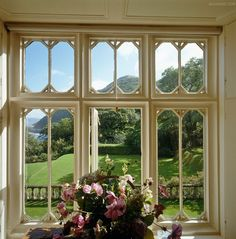 View through the window of a country drawing room to the garden and the English landscape beyond