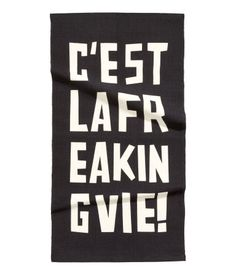 Rectangular, woven cotton rug with printed text motif at front.