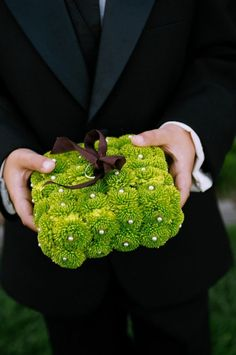 Ring bearer pillow composed of green button mums and filled with brown silk ribbon