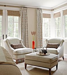 Outfitted for rest, relaxation, and connection to the outdoors, a neutral bedroom surrounded with windows is a soft, serene space to begin and end each day. French doors open to a balcony overlooking the backyard, and roomy chairs offer an inviting spot to survey views./