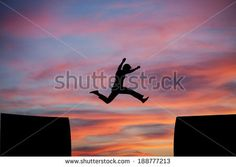 man jumping a gap in sunset sky  - stock photo
