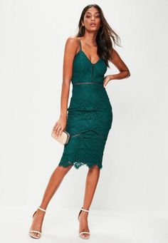 This dress features a deep green hue, lace fabric with ladders details and a midi length. Finished with adjustable straps and a split hem.