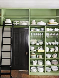 This kitchen's floor-to-ceiling shelves hold tons of tableware. Wall color: Land of Liberty by Benjamin Moore.    #kitchens #storage