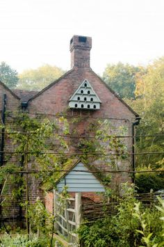 A beautiful dovecote on the side of a brick cottage. Try Farrow and Ball's Pale Powder for similar.