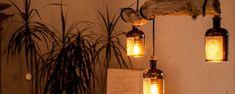 Die DIY Lampe aus Treibholz gibt durch die Gin Flaschen ein warmes Licht