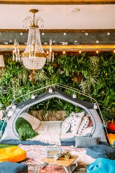 Living wall + layered kilim rugs + chandelier + tent in the living room = my idea of glamping. #sponsored