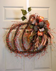 """A grapevine pumpkin shape with orange gypsum. Tied with a six patterned Terri Bow and grassy accents. Measures 27"""" H X 27""""W."""