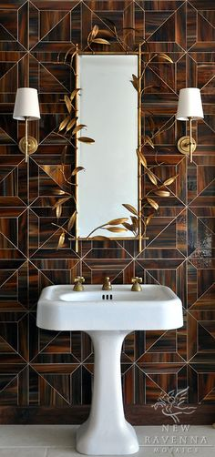 gold mirror and sconces hung on wall of tortoise shell tiles