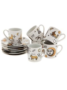 A set six white side plates and six mugs from Fornasetti featuring a gold-tone print design of astrology artwork, each piece displaying a different design