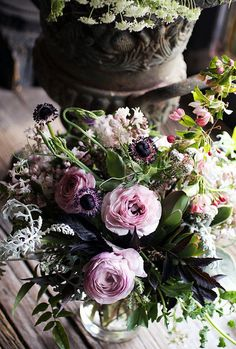 purple, pink and gray flower arrangement of ranunculus, lilac, sweet peas, geranium, jasmine, anemones, dusty miller and crabapple