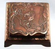 Wonderful Copper Art Nouveau Stamp Box  Great little footed stamp box! Crafted from copper with a silvered interior, the top features a finely detailed little bird perched atop a flowering branch. The branch extends to the edges, which morph into a pair of scaled water creatures – perhaps dragons? The base is stamped with more flower designs.