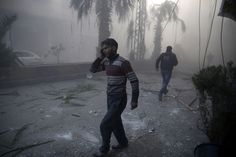 Sameer Al-Doumy, Syria, 2015, Agence France-Presse A wounded man walks out of a dust cloud following reported airstrikes in the town of Hamouria, Syria, 09 December 2015.