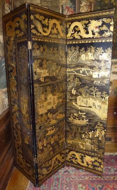 Chinese export lacquer draught screen with three leaves. Decorated with black and gold dragon border figures in garden, tea houses and boats on lakes, the reverse similarly decorated.