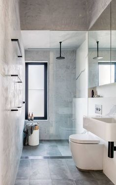 Black, white and grey bathroom: grey marbled tiles, black tapware, black towel rails, long channel floor grate, frameless shower screen, linear exhaust fan, concealed-cistern toilet, wall-hung basin with black bottle trap, mirror cabinets, recessed shelf, narrow window in shower, window ledge as shelf