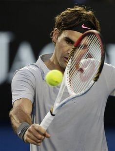Switzerland's Roger Federer makes backhand return to Australia's Bernard Tomic during their third round match at the Australian Open tennis championship in Melbourne, Australia, Saturday, Jan. 19, 2013. (AP Photo/Andy Wong)