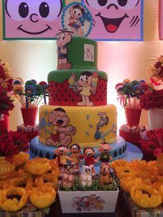 O bolo cenográfico da mesa, da Katia Pellegrini (www.facebook.com/katia.pellegrini.50), tinha três andares e cada um deles representava um personagem da Turma da Mônica. Um jardim com grama artificial servia de apoio para doces modelados, da chef Aline Leone, com sabor de trufa de chocolate. A Thanks - Grife de Festas também colocou personagens da Turma da Mônica de biscuits em cima de potinhos de doce de leite