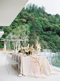 This dried flower backdrop for a destination wedding villa ceremony is giving us life! With a sun-kissed ocean view, a soft pink tablescape and natural decor elements scattered throughout, this Thailand wedding inspiration is all things glorious! See it all on Ruffled now. #phuketwedding #infinitypoolwedding #filmweddingphotographer